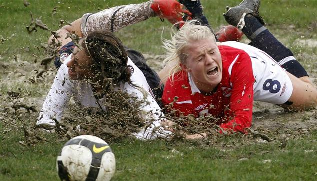 Solvieg Gulbrandson of Norway in the mud with USA's Carli Lloyd